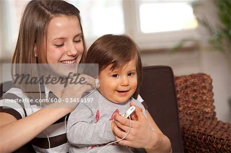 Teenage Girl with Baby Boy Listening to MP3 Player, Mannheim, Baden-Wurttemberg, Germany Stock Photo - Premium Royalty-Free, Image code: 600-03456197