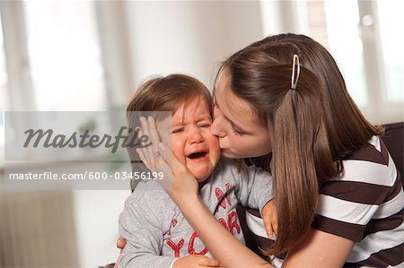 Teenage Girl Kissing Crying Baby Boy, Mannheim, Baden-Wurttemberg, Germany Stock Photo - Premium Royalty-Free, Image code: 600-03456199