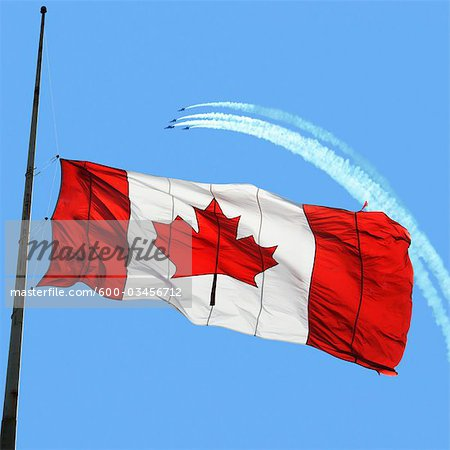 Canadian Flag at Half Mast, Snowbirds in the Background Stock Photo - Premium Royalty-Free, Image code: 600-03456712