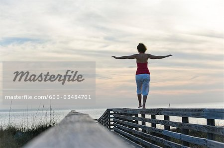 Woman Balancing on Wooden Railing, Honeymoon Island State Park, Florida, USA Stock Photo - Premium Royalty-Free, Image code: 600-03484701