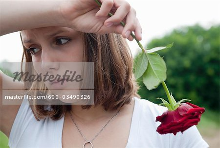 Teenage Girl Holding a Red Rose Stock Photo - Premium Royalty-Free, Image code: 600-03490326