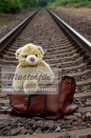 Teddy Bear and Suitcase on Train Tracks Stock Photo - Premium Royalty-Free, Image code: 600-03490332