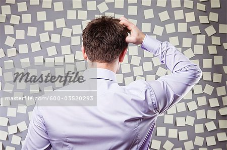 Businessman Looking at a Wall Full of Self Adhesive Notes Stock Photo - Premium Royalty-Free, Image code: 600-03520293