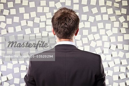 Businessman Looking at a Wall Full of Self Adhesive Notes Stock Photo - Premium Royalty-Free, Image code: 600-03520294