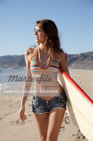 Young Woman holding Surfboard Walking on Beach, Zuma Beach, California, USA Stock Photo - Premium Royalty-Free, Image code: 600-03520499