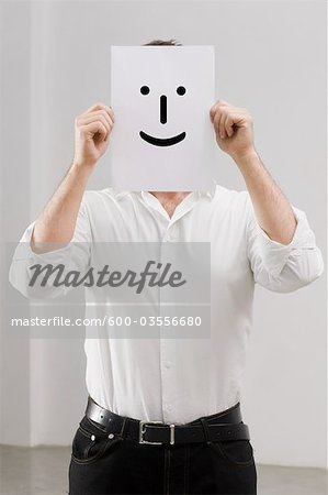 Businessman Holding Paper Face Stock Photo - Premium Royalty-Free, Image code: 600-03556680