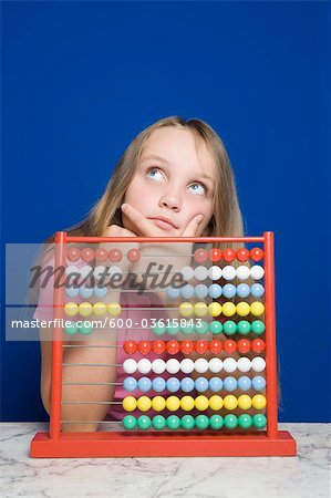 Young Girl Counting With Abacus Stock Photo - Premium Royalty-Free, Image code: 600-03615843