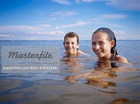 Boy and Girl Swimming, Lake Wanapitei, Sudbury, Ontario, Canada Stock Photo - Premium Royalty-Free, Image code: 600-03621294