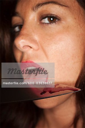 Woman Licking Blood off a Knife Stock Photo - Premium Royalty-Free, Image code: 600-03638627