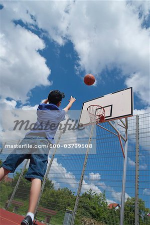 Boy Playing Basketball Stock Photo - Premium Royalty-Free, Image code: 600-03799508