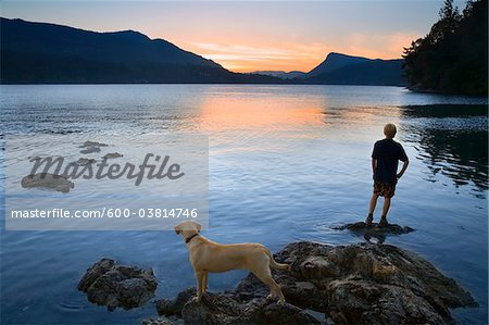 Teenager and Dog looking at Sunset, Fulford Harbour, Salt Spring Island, British Columbia, Canada Stock Photo - Premium Royalty-Free, Image code: 600-03814746
