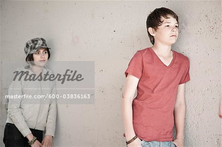 Boy and Girl Leaning on Wall Stock Photo - Premium Royalty-Free, Image code: 600-03836163