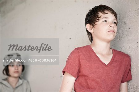 Boy and Girl Leaning on Wall Stock Photo - Premium Royalty-Free, Image code: 600-03836164