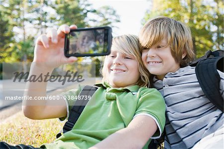 Boys taking Picture with Camera Phone Stock Photo - Premium Royalty-Free, Image code: 600-03848739