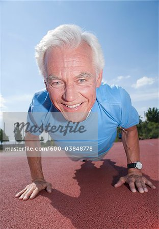 Man Exercising Outdoors on Track Stock Photo - Premium Royalty-Free, Image code: 600-03848778