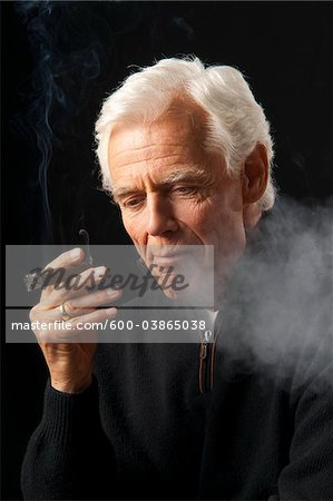 Man Smoking Cigar Stock Photo - Premium Royalty-Free, Image code: 600-03865038
