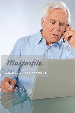 Man using Laptop and Cordless Phone Stock Photo - Premium Royalty-Free, Image code: 600-03865041