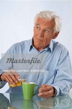 Man adding Alcohol to his Coffee Stock Photo - Premium Royalty-Free, Image code: 600-03865052