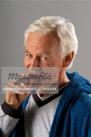 Man Smoking Cigar with Lipstick Kiss on Cheek Stock Photo - Premium Royalty-Free, Image code: 600-03865084