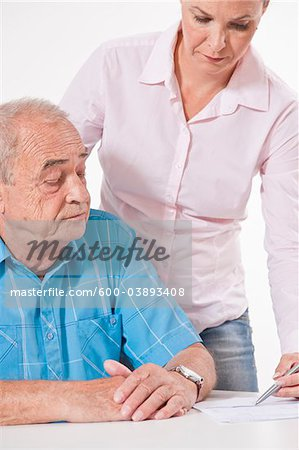 Man and Woman Discussing Paperwork Stock Photo - Premium Royalty-Free, Image code: 600-03893408