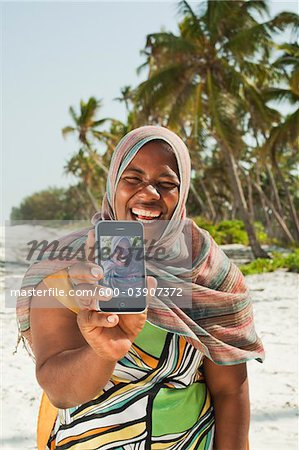 Woman Showing Snapshots, Nyota Beach, Unguja, Zanzibar, Tanzania Stock Photo - Premium Royalty-Free, Image code: 600-03907372