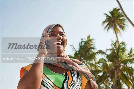 Woman Using Cell Phone, Nyota Beach, Unguja, Zanzibar, Tanzania Stock Photo - Premium Royalty-Free, Image code: 600-03907373