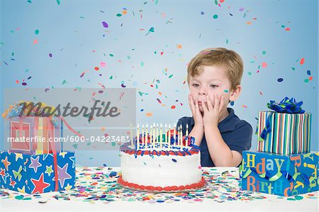 Young Boy with Birthday Presents and Making a Wish before Blowing Out Candles on Birthday Cake Stock Photo - Premium Royalty-Free, Image code: 600-04223481