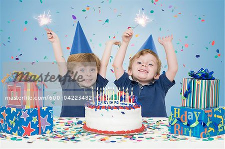 Twin Boys holding Sparklers with Birthday Cake and Presents Stock Photo - Premium Royalty-Free, Image code: 600-04223482