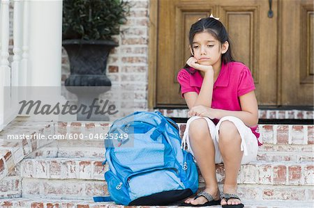 Girl with Backpack Sitting on Steps Stock Photo - Premium Royalty-Free, Image code: 600-04625349