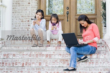 Mother using Laptop and Daughters using Handheld Video Games Stock Photo - Premium Royalty-Free, Image code: 600-04625356