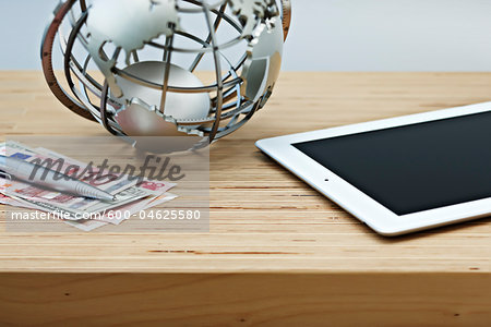Desk with Currency, Globe and Tablet Computer Stock Photo - Premium Royalty-Free, Image code: 600-04625580