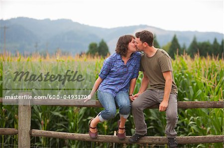 Couple Sitting on Fence Kissing, Sauvie Island, Oregon, USA Stock Photo - Premium Royalty-Free, Image code: 600-04931708