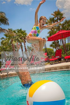 Father Tossing Daughter into Pool, PGA National Resort and Spa, Palm Beach Gardens, Florida, USA Stock Photo - Premium Royalty-Free, Image code: 600-05181872