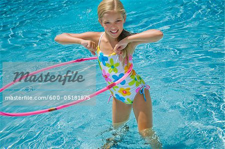 Girl in Pool with Hula Hoop Stock Photo - Premium Royalty-Free, Image code: 600-05181875