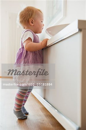 Baby Girl looking in Bowl Stock Photo - Premium Royalty-Free, Image code: 600-05181884