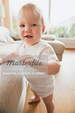 Baby Girl Standing by Sofa Stock Photo - Premium Royalty-Free, Image code: 600-05181885