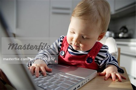 Baby Girl Playing with Laptop, London, England Stock Photo - Premium Royalty-Free, Image code: 600-05451157