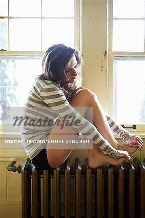 Woman sitting on Radiator by Window Stock Photo - Premium Royalty-Free, Image code: 600-05780990