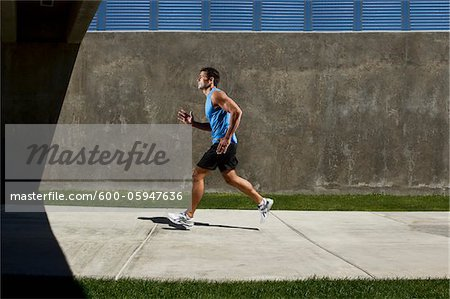 Man Running on Sidewalk Stock Photo - Premium Royalty-Free, Image code: 600-05947636