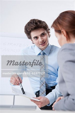 Young Businessman giving Presentation to Businesswoman Stock Photo - Premium Royalty-Free, Image code: 600-05973117