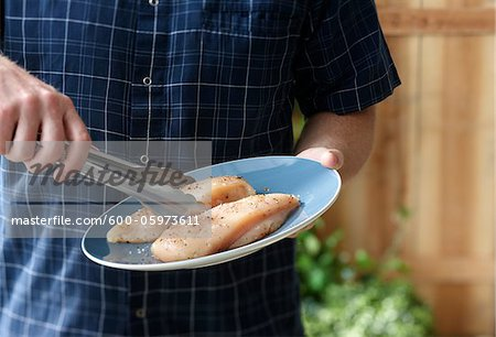 Man putting Chicken on Barbeque Stock Photo - Premium Royalty-Free, Image code: 600-05973611