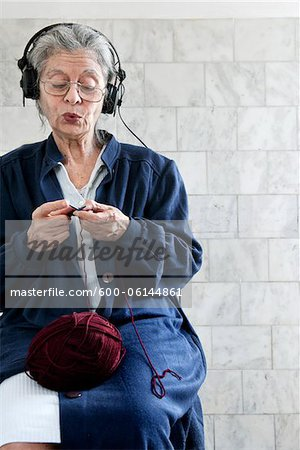 Woman Knitting and Listening to Headphones Stock Photo - Premium Royalty-Free, Image code: 600-06144861