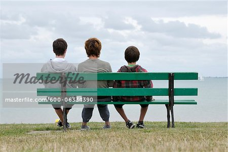 Back View of Mother and Sons Sitting on Park Bench, Ile de Re, France Stock Photo - Premium Royalty-Free, Image code: 600-06334390
