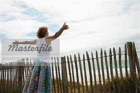 Woman with Open Arms at the Beach, Camaret-sur-Mer, Crozon Peninsula, Finistere, Brittany, France Stock Photo - Premium Royalty-Free, Image code: 600-06382809
