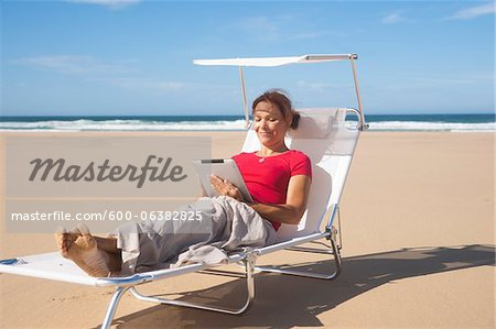 Woman Using Tablet at the Beach, Camaret-sur-Mer, Crozon Peninsula, Finistere, Brittany, France Stock Photo - Premium Royalty-Free, Image code: 600-06382825
