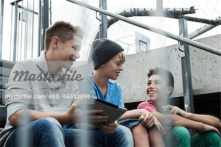 Boys with Tablet Sitting on Bleachers, Mannheim, Baden-Wurttemberg, Germany Stock Photo - Premium Royalty-Free, Image code: 600-06382856