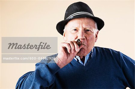 Portrait of Senior Man Smoking Cigar Stock Photo - Premium Royalty-Free, Image code: 600-06382926