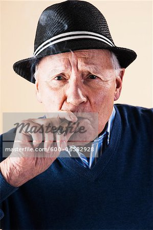 Portrait of Senior Man Smoking Cigar Stock Photo - Premium Royalty-Free, Image code: 600-06382928