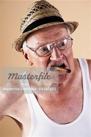 Portrait of Senior Man Smoking Cigar Stock Photo - Premium Royalty-Free, Image code: 600-06382933