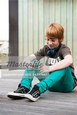 Boy with MP3 Player Outdoors, Mannheim, Baden-Wurttemberg, Germany Stock Photo - Premium Royalty-Free, Image code: 600-06397447